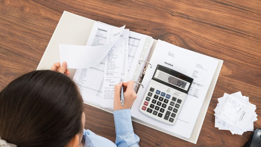 Businesswoman Calculating Tax At Desk With Calculator In Office.