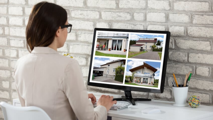 Rear View Of A Businesswoman Looking At House Photos On Computer In Office.