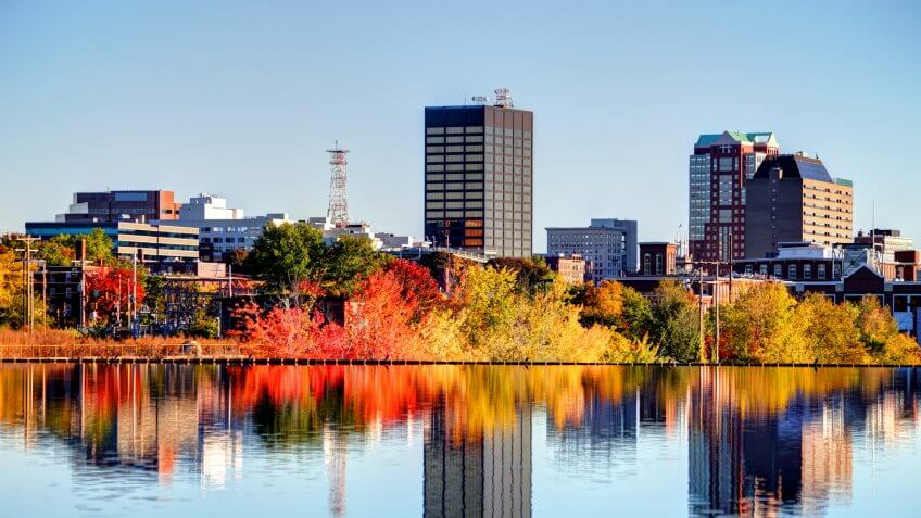 Manchester New Hampshire skyline along the banks of the Merrimack River in autumn.