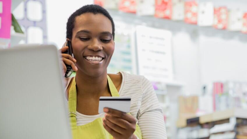 Female small business owner paying for orders over phone.