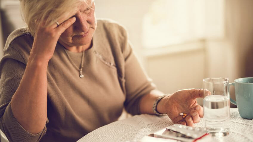 Old woman holding her head in pain while about to take medicines.
