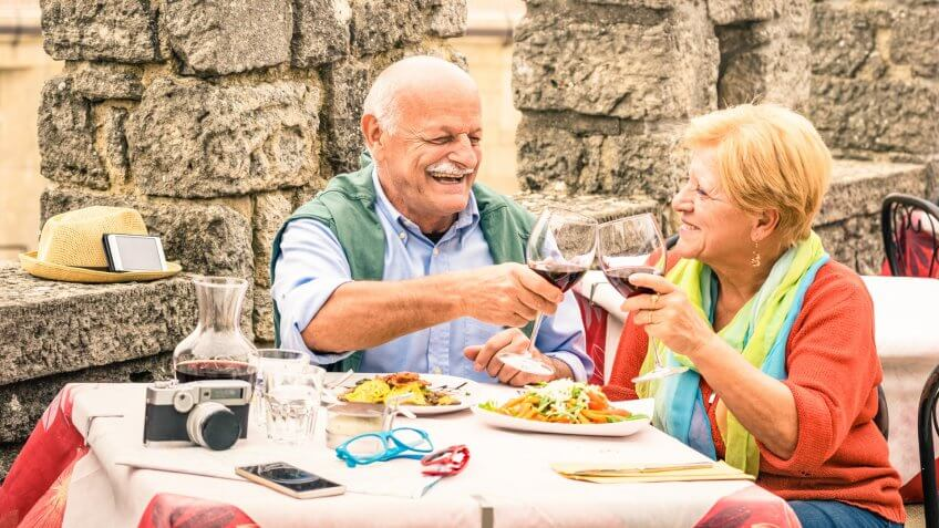 Senior couple having fun and eating at restaurant during travel - Mature man and woman wife in old city town bar during active elderly vacation - Happy retirement concept with retired people together.