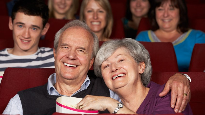 Senior Couple Watching Film In Cinema Eating Popcorn Hugging Each Other Smiling.