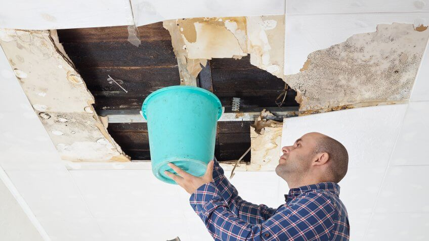 man-collecting-water-bucket-ceiling-panels