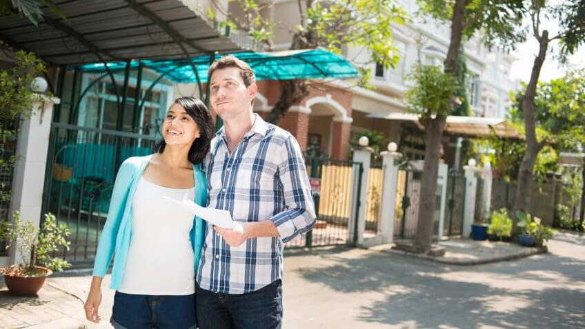 Young couple gladly looking at the house.