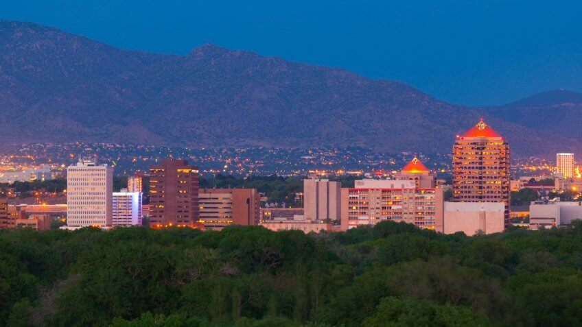 Downtown Albuquerque skyline at dusk with the Sandia Mountains in the background.