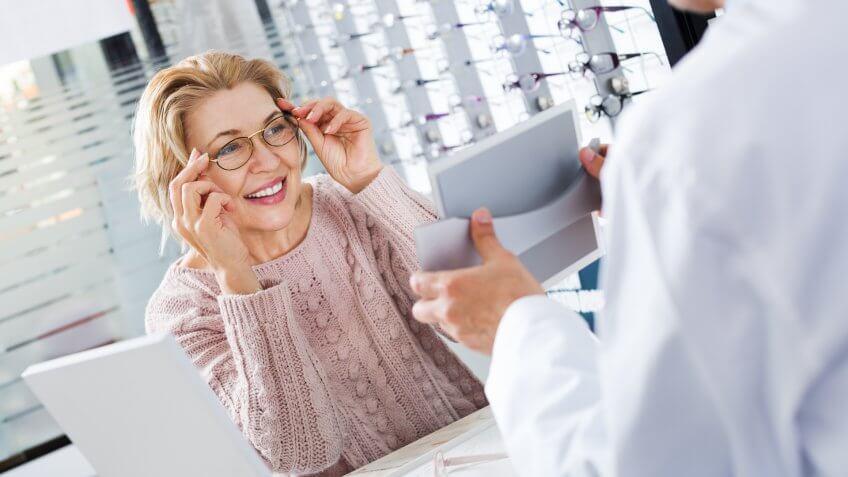 mature-ophthalmologist-female-pensioner-choosing-glasses
