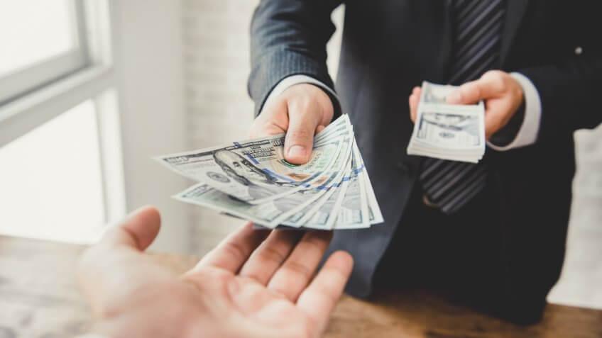 businessman-giving-money-us-dollar-bills