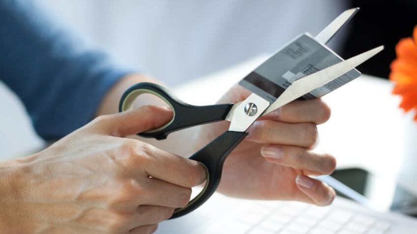 Female hands cutting a credit card with scissors.