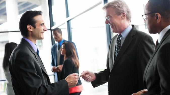 Smiling businessmen exchanging business cards at a networking event in a bright glass office.