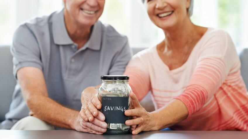 Shot of a senior couple proudly posing with their savings jar.