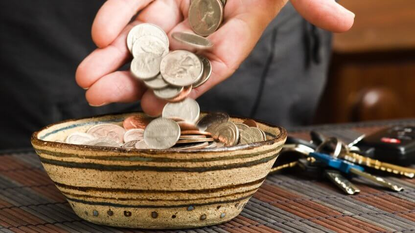 man placing pocket change in bowl.