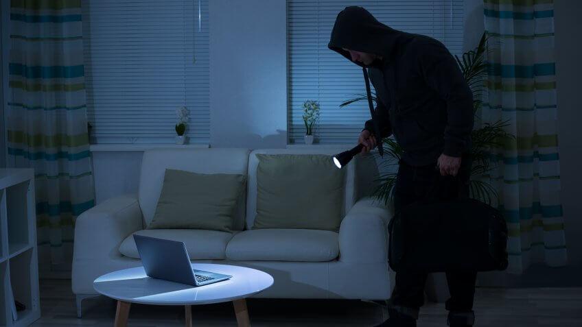 full-length-robber-holding-flashlight-over