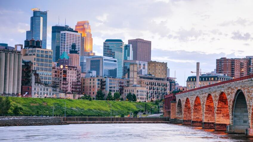 Downtown Minneapolis, Minnesota at night time as seen from the famous stone arch bridge.