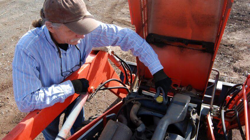 man-removing-radiator-cap-on-tractor