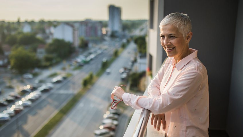 Happy mature woman standing on a penthouse terrace and looking at view.