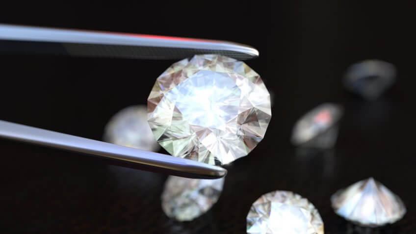 Tweezers holding a white, perfect diamond.