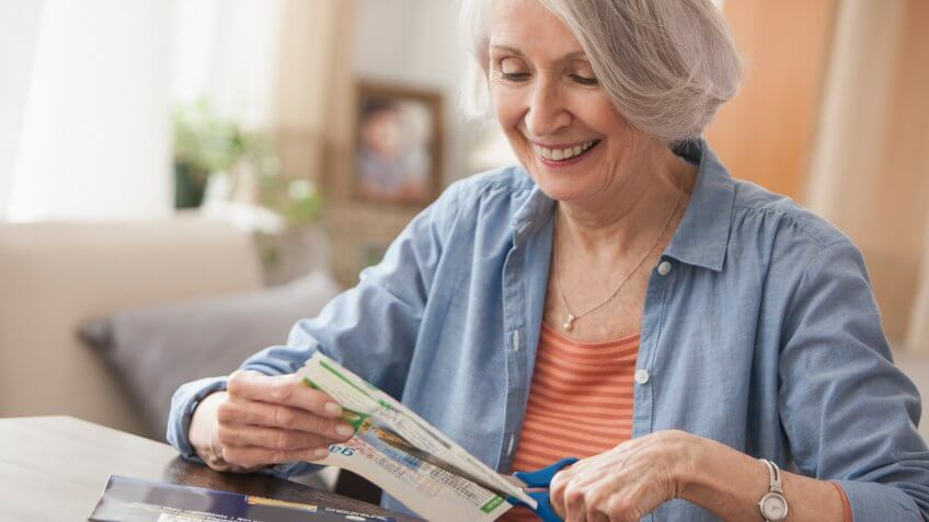 Senior woman clipping coupons.