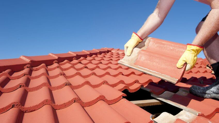 roof-repair-worker-yellow-gloves-replacing