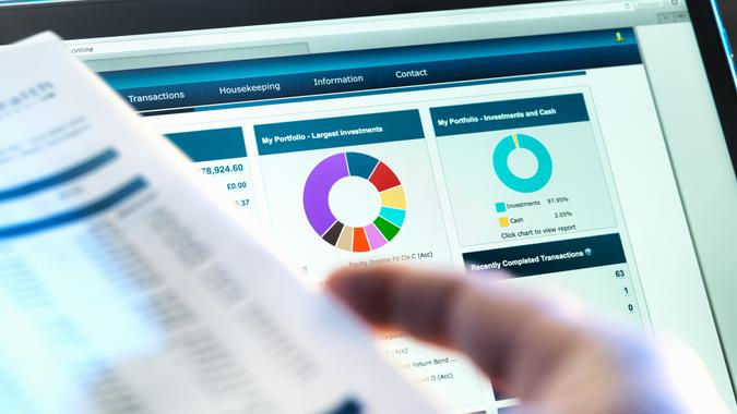 Investor checking performance of financial portfolio online whilst reviewing investment statement.
