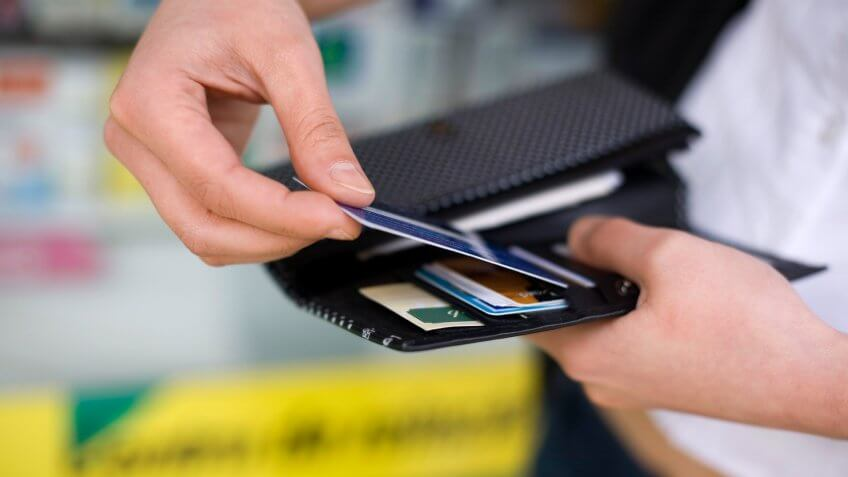 Close-up of a woman getting a credit card out of her wallet.