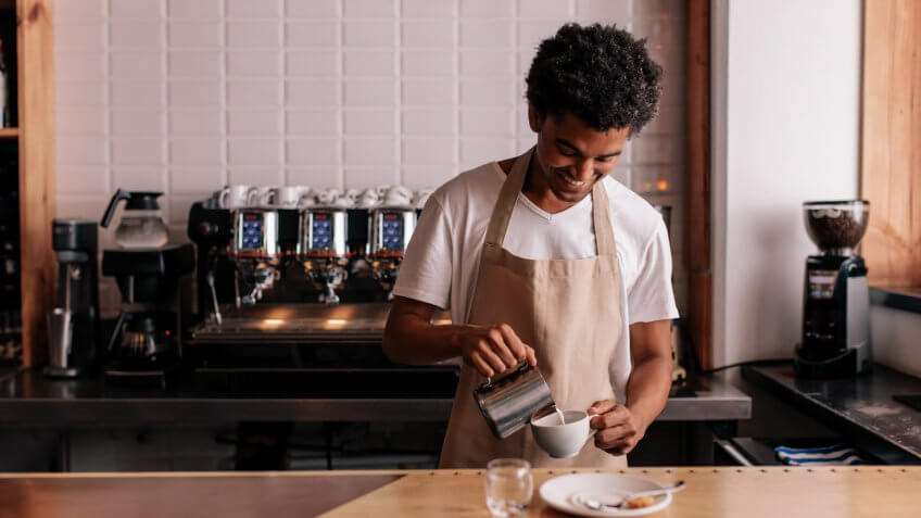young-african-man-pouring-milk-into-coffee