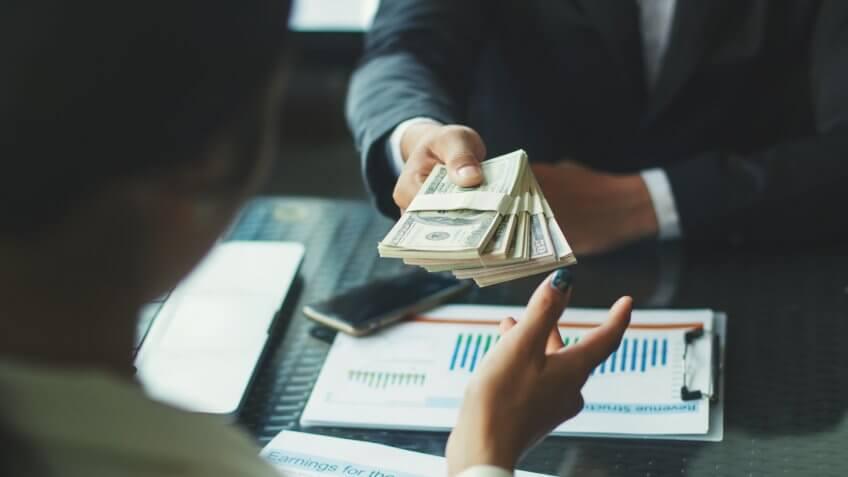 hand-giving-money-united-states-dollars