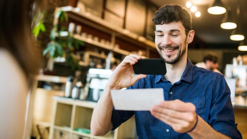 "A smiling man takes a picture with his smart phone of a check or paycheck for digital electronic depositing, also known as ""Remote Deposit Capture""."