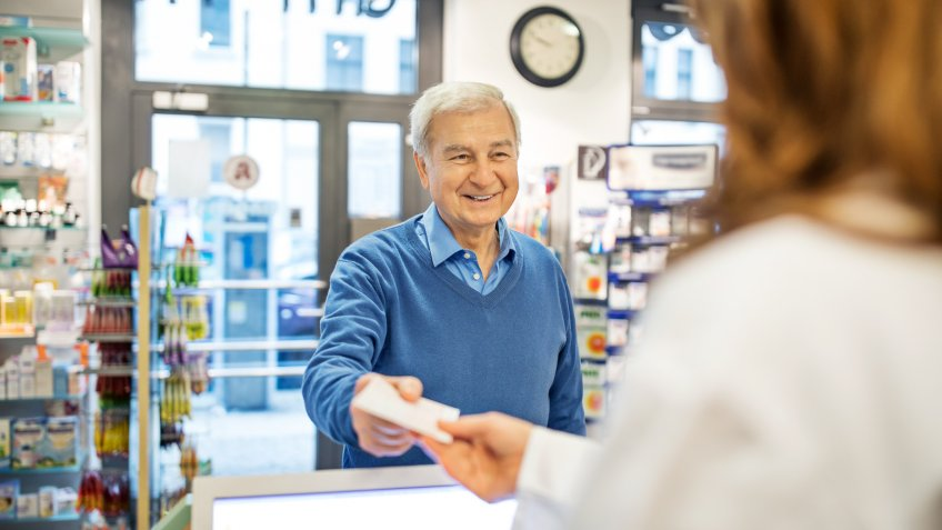 Smiling senior man giving prescription to female pharmacist in store.