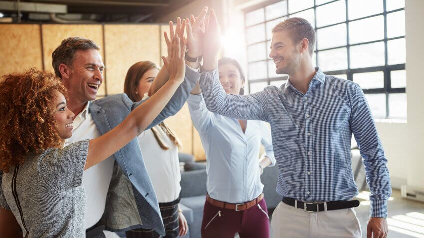 group of businesspeople high fiving in the office