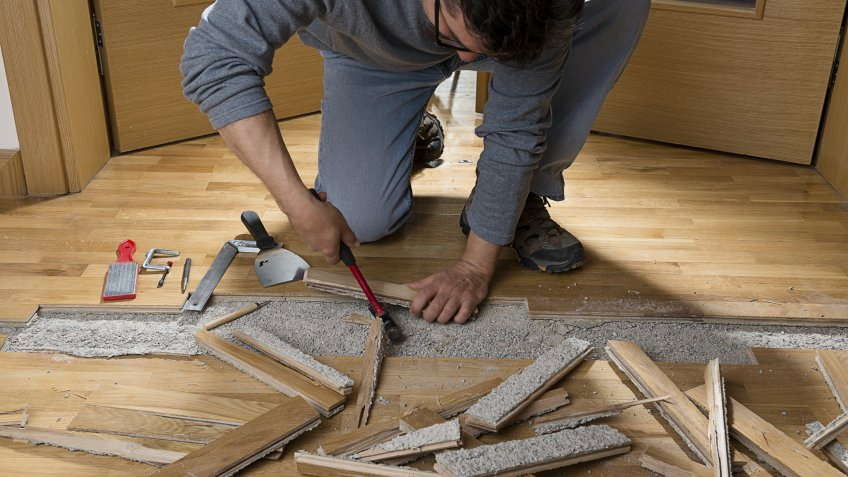 manual-worker-disassembling-wooden-floor-ruined