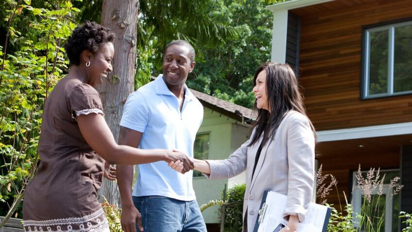Real estate agent greeting couple at house.