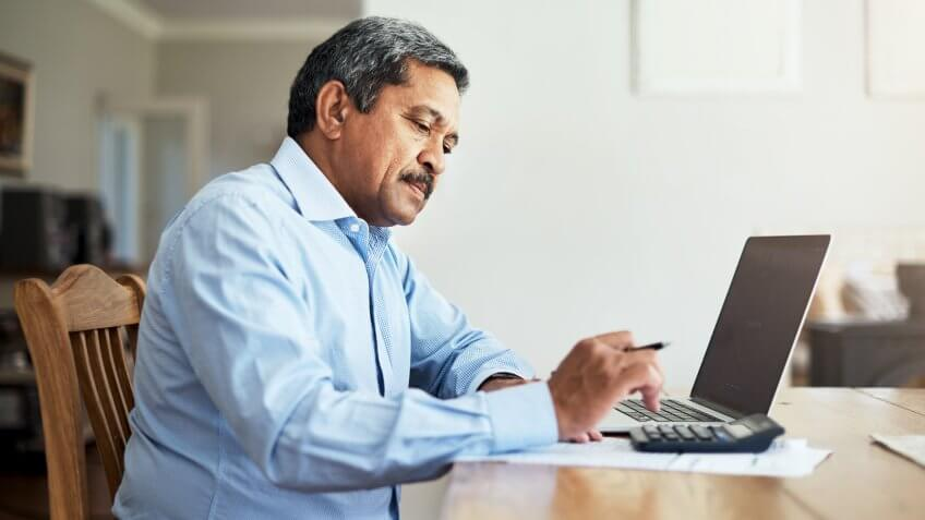 Cropped shot of a senior man using a laptop to do the household finances.