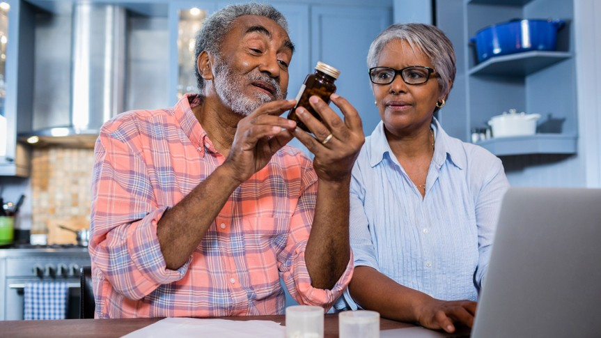 Man looking at medicine while sitting by woman using laptop in kitchen at home.