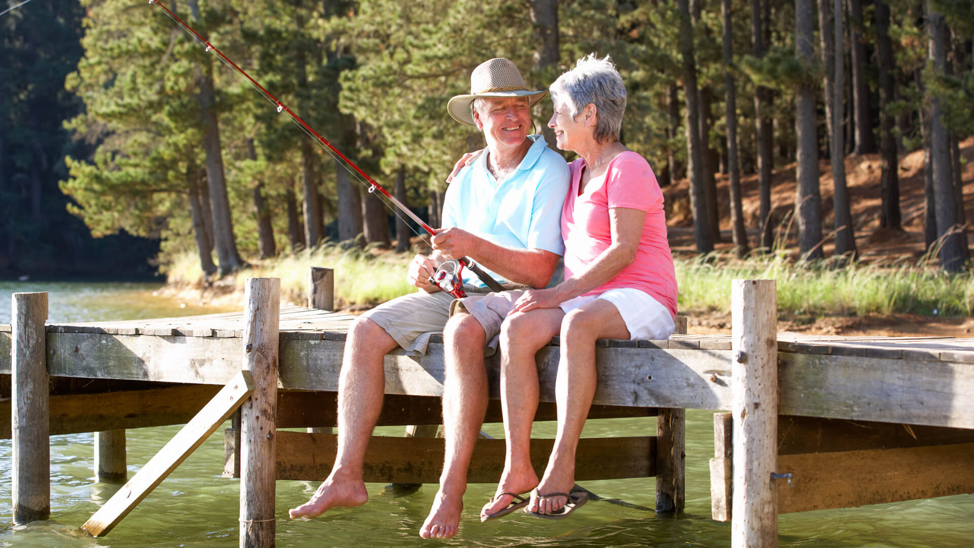 Senior couple sitting on jetty together fishing, enjoying their time in retirement.