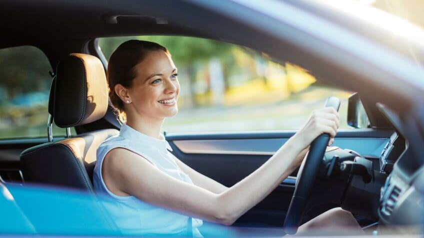 Close up photo of a businesswoman driving a car.