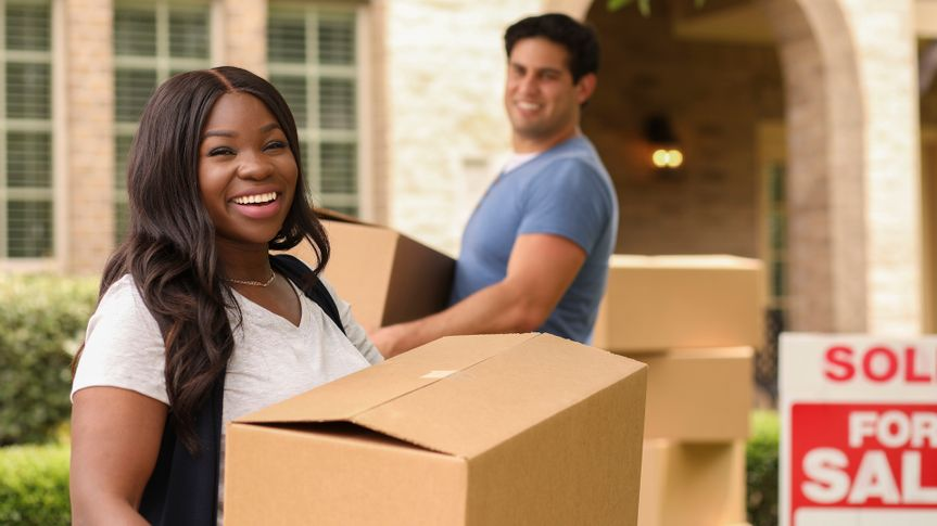 Mixed race family of African and Latin descent moving boxes into a new home.
