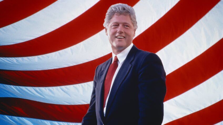 President William Jefferson Clinton in front of American flag stripes.