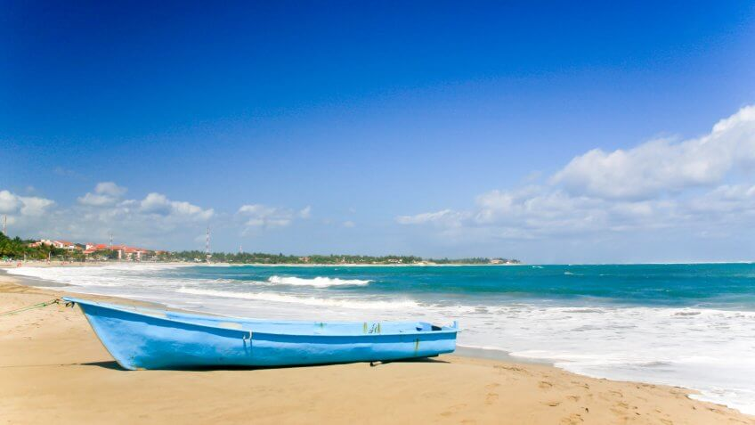 A powder blue boat pulled up on the beach of Cabarete Bay, Cabarete, Dominican Republic.