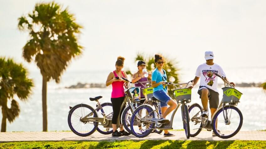 Miami Beach, USA  - January 5, 2013: Group of Young people cycling on the beach.