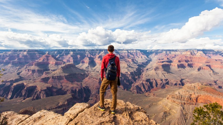 Travel in Grand Canyon, man Hiker with backpack enjoying view, USA.
