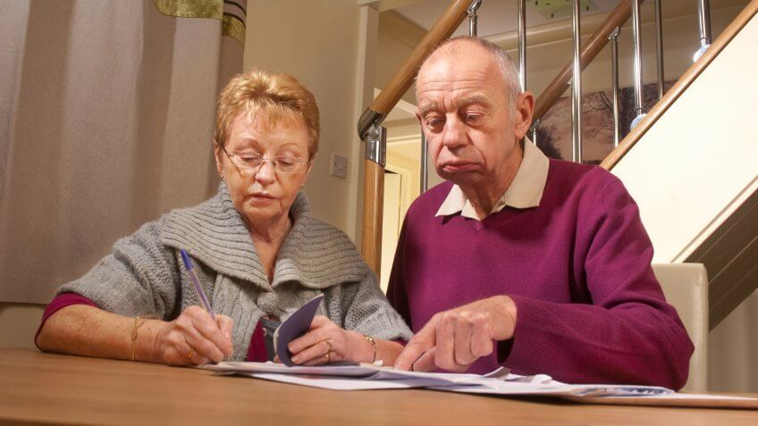 senior couple pay bills.