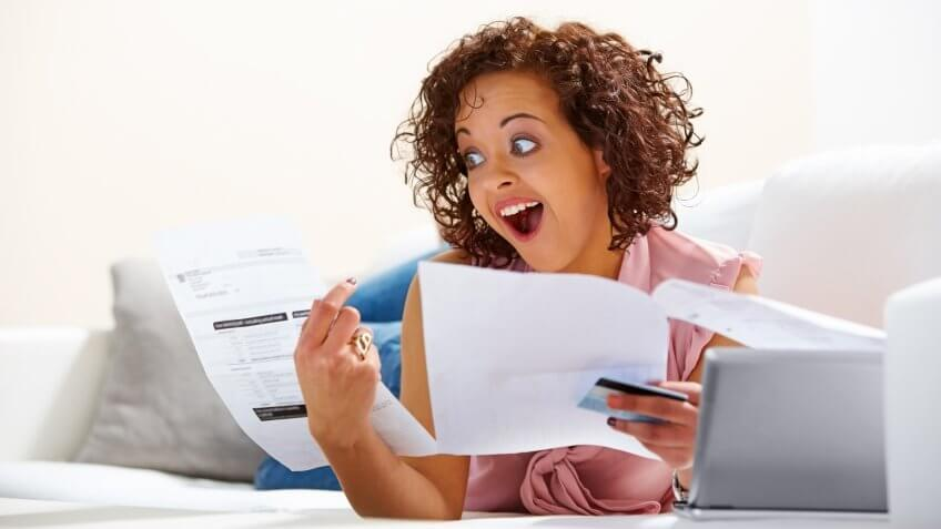 Image of young lady looking excited after looking at her credit card bill.