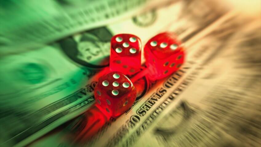 Dollar with dices illuminated with low light in radial blur.