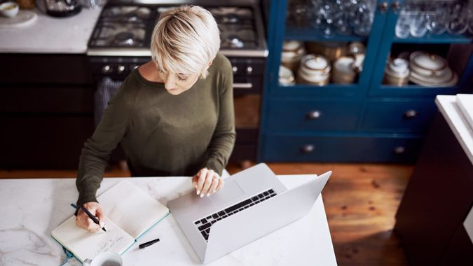 High angle shot of a mature woman writing in a notebook while working on a laptop at home.