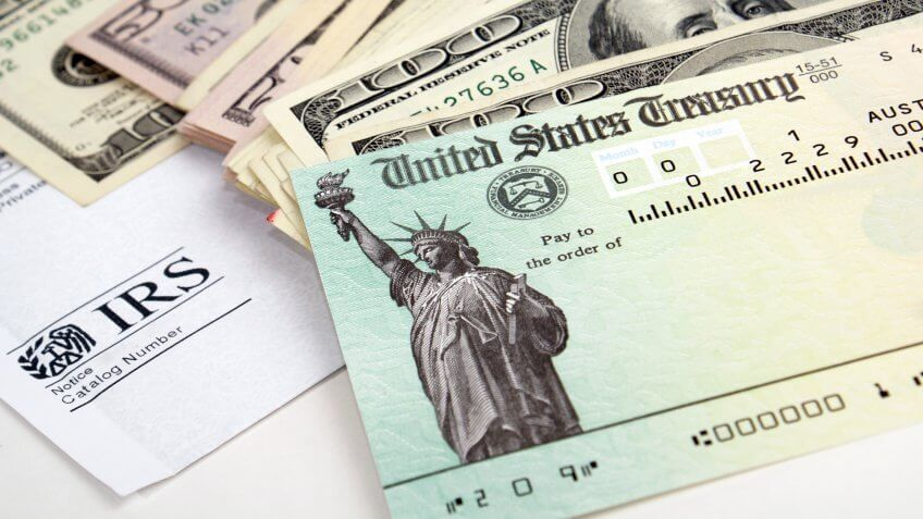 Close-up of tax return check and USA currency.