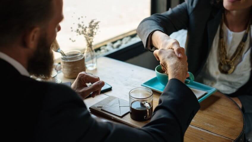 Business agreement handshake at coffee shop.