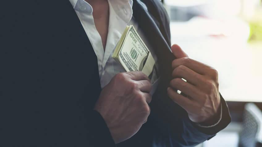 Business man hiding money in pocket.