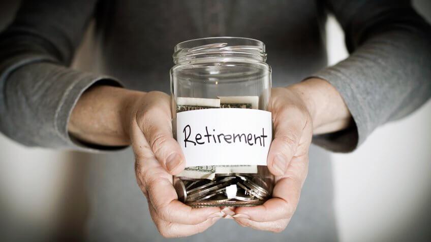 Retirement Savings Concept : Senior woman hands holding jar full of money - vignette.