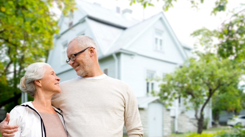 family, age, home, real estate and people concept - happy senior couple hugging over living house background.